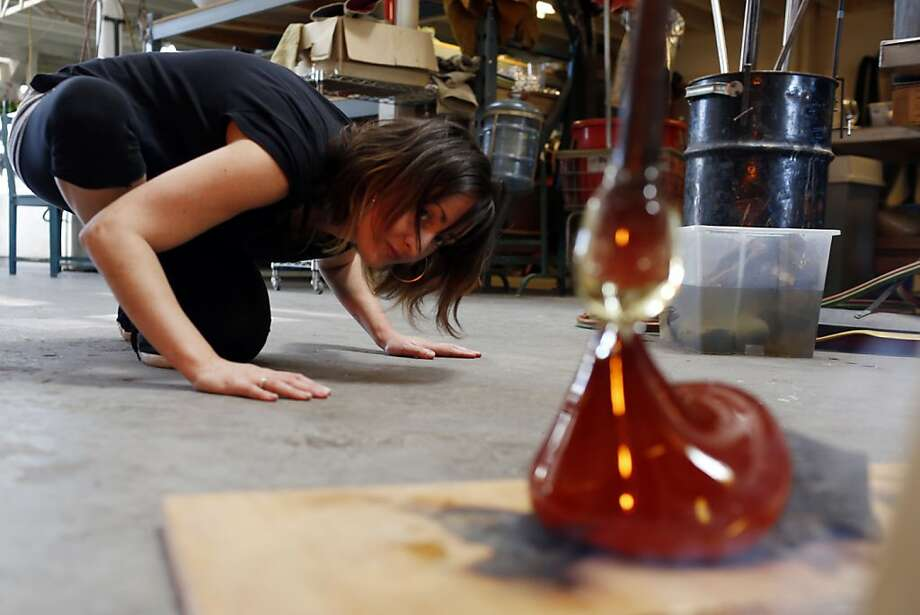 Heather Palmer watches for the glass to touch bottom as it flows over the wood. Photo: Ian C. Bates, The Chronicle