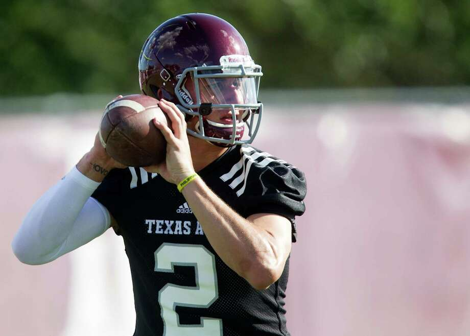 Texas A&M quarterback and Heisman Trophy winner Johnny Manziel throws during football practice, Monday, Aug. 5, 2013, in College Station, Texas. The NCAA has started an investigation as to whether Manziel received payment for signing hundreds of autographs on photos and sports memorabilia in January. (AP Photo/Patric Schneider) Photo: Patric Schneider, Associated Press / FR170473 AP