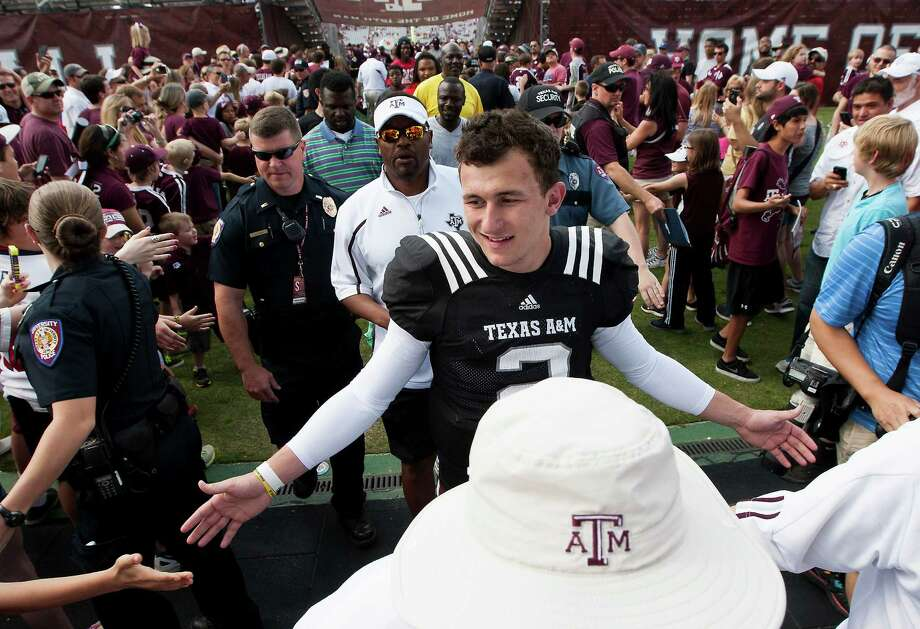 Texas A&M quarterback Johnny Manziel is greeted by fans as he walks of the field after the Texas A&M Aggies Maroon and White spring football game on Saturday, April 13,  2013, in College Station, Texas. (AP Photo/ Patric Schneider) Photo: Associated Press / FR170473 AP