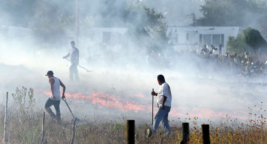 Residents use shovels to fight a grass fire off IH-35 South Monday Aug. 5, 2013 near Natalia, Tx.