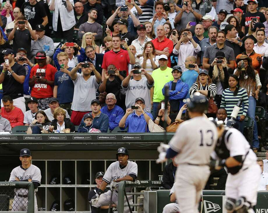 Fans watch and take pictures as New York Yankees' Alex Rodriguez bats for the first time in 2014 against the Chicago White Sox in a baseball game at US Cellular Field in Chicago on Monday, Aug.,5, 2013. (AP Photo/Charles Cherney) ORG XMIT: CXS112 Photo: Charles Cherney / FR170067 AP