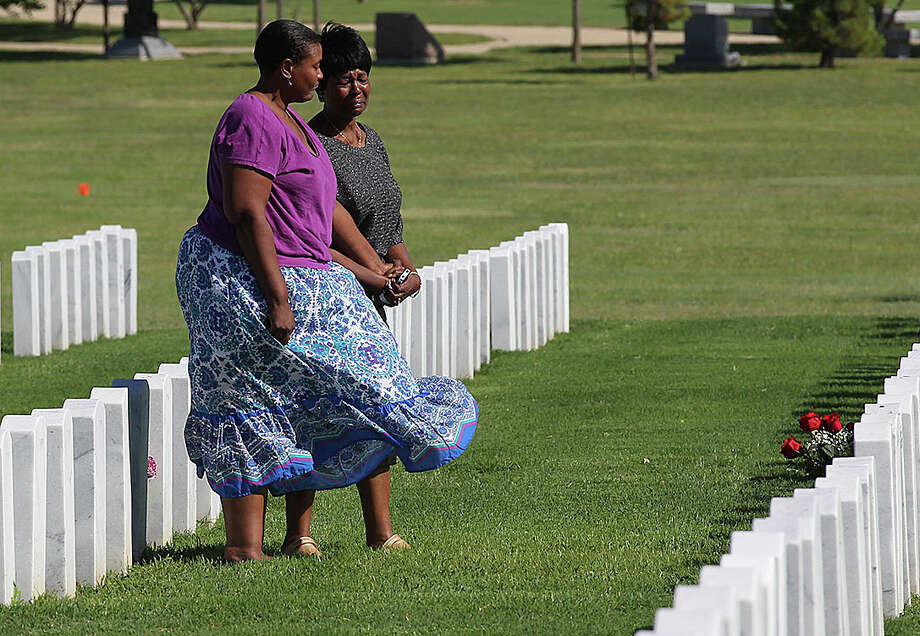 With her daughter, Shannon Graham, left, Tanya Graham visits her husband's grave at the Central Texas State Veterans Cemetery in Killeen.  Her husband, Willie, a Vietnam vet, was so upset by the Fort Hood massacre he wanted to re-enlist, she said. Photo: Staff / ©2013 San Antonio Express-News