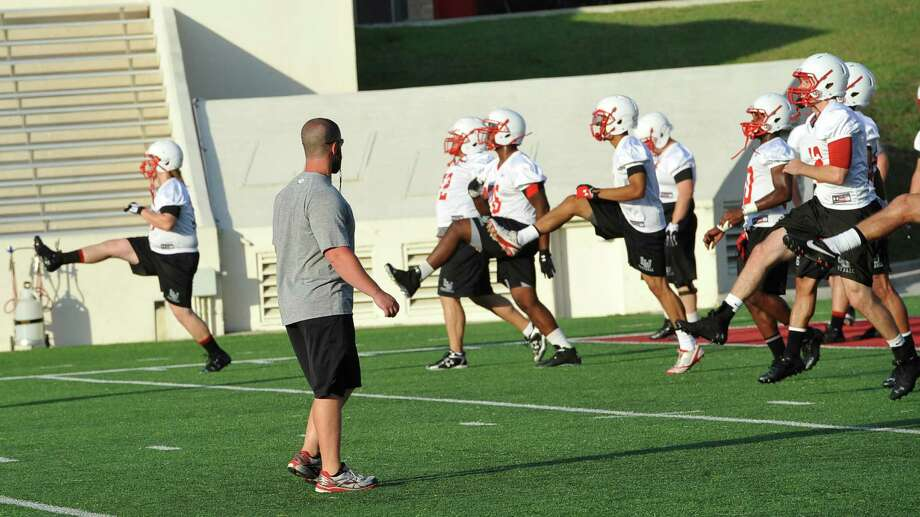 Strength and conditioning coach Josh Miller, left, puts the players through warm-up drills. Lamar University conducted its first practice of the 2013 season Monday August 5, 2013. It was held inside Provost Umphrey Stadium, and the players were not wearing any pads. The battle for the starting quarterback position will be important, because Caleb Berry (#12) and Ryan Mossakowski (#18) have more competition with Houston-transfer Rex Dausin (#14) coming in, as well as some freshmen.  Dave Ryan/The Enterprise Photo: Dave Ryan