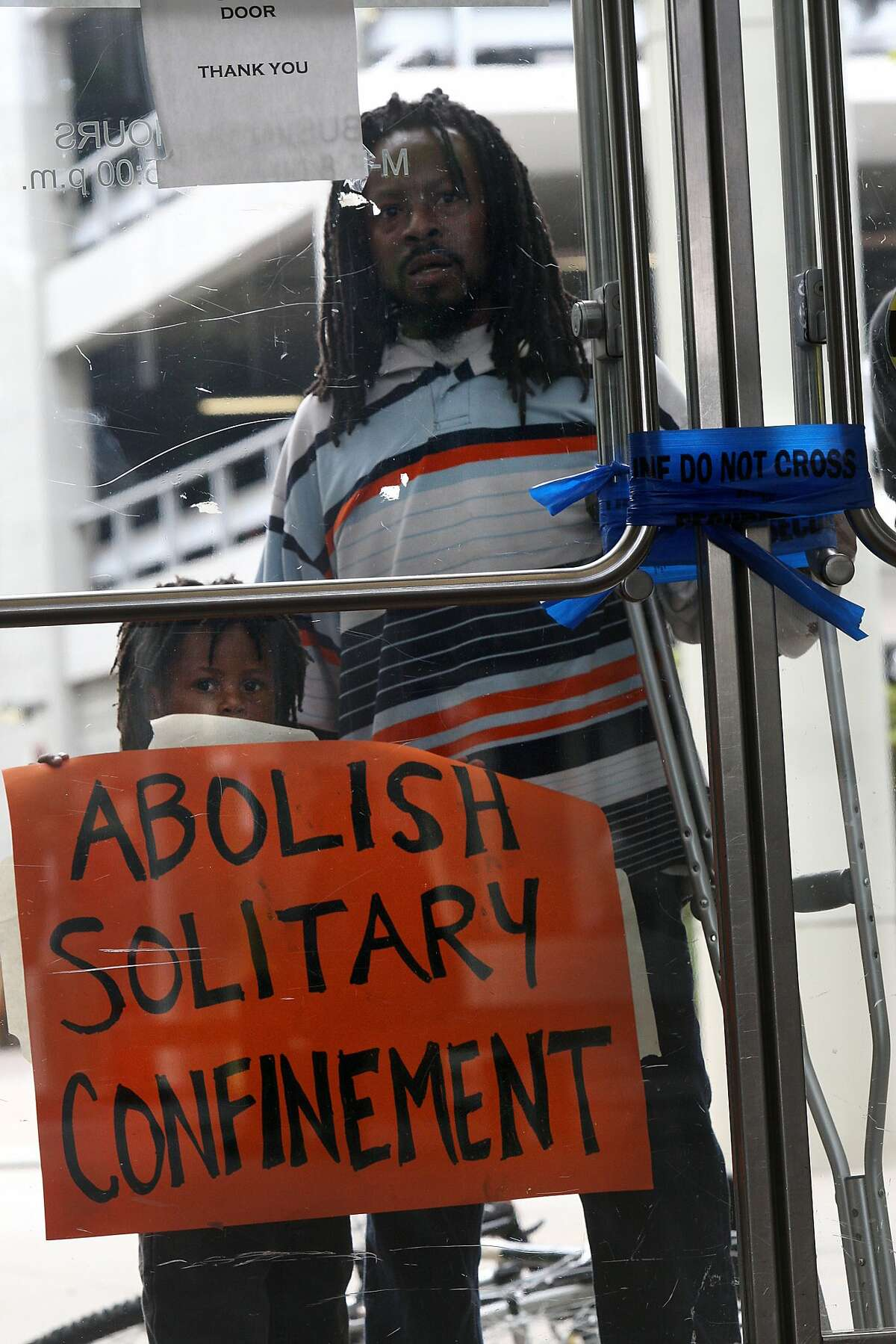 Community activist Jabari Shaw with his five year old son Safir Shaw from Oakland look through the Oakland State Building in Oakland as protesters chant in the lobby on Monday, August 5, 2013. Protesters are in solidarity with the California Prisoner Hunger Strike asking five demands--long term solitary confinement, comprehensive changes in