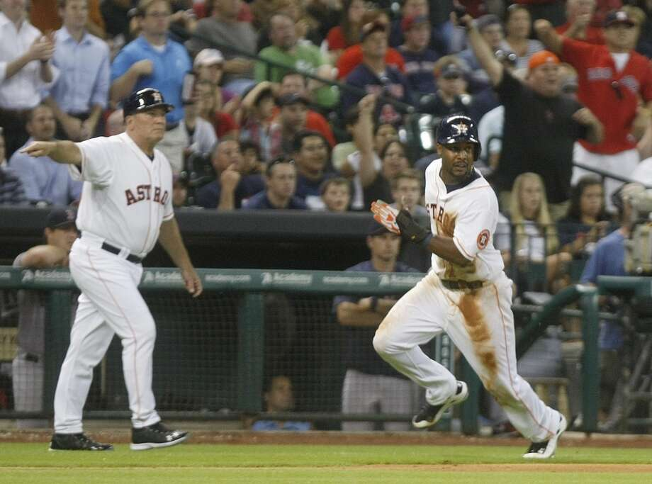 Astros third base coach Dave Trembley waves home left fielder L.J. Hoes to score the first one. Photo: Johnny Hanson, Houston Chronicle
