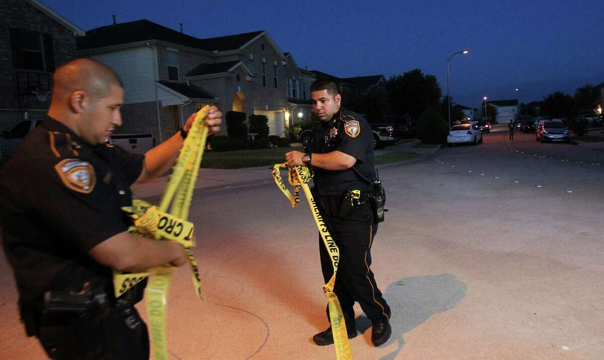 Harris County Sheriff's Officers get ready to open the closed street as investigators conclude their on location investigation where a 3 year-old was shot as a result of a feud along Cypress Gully Drive on Tuesday, Aug. 6, 2013, in Cypress.