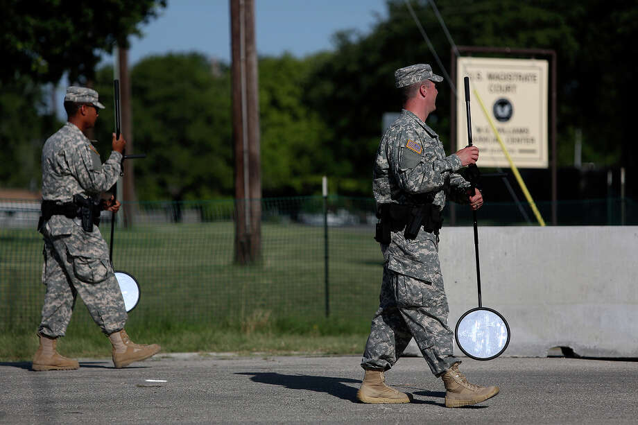 Soldiers walk with undercarriage inspection mirrors after inspecting a car arriving at the Lawrence H. Williams Judicial Center as the trial for Maj. Nidal Hasan begins at Fort Hood in Killeen on Tuesday, August 6, 2013. Photo: Lisa Krantz, San Antonio Express-News / San Antonio Express-News