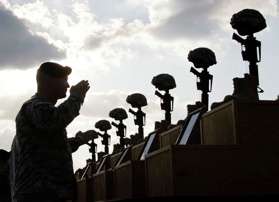 FILE- In this Nov. 10, 2009, file photo, soldiers salute as they honor victims of the Fort Hood shooting at a memorial service at Fort Hood, Texas. Maj. Nidal Hasan will stand trial, in a court-martial that starts Tuesday, Aug. 6, 2013, for the shooting rampage at Fort Hood, Texas, that left 13 people dead and more than 30 people wounded on Nov. 5, 2009. (AP Photo/Donna McWilliam, File) Photo: Donna McWilliam, STF / AP