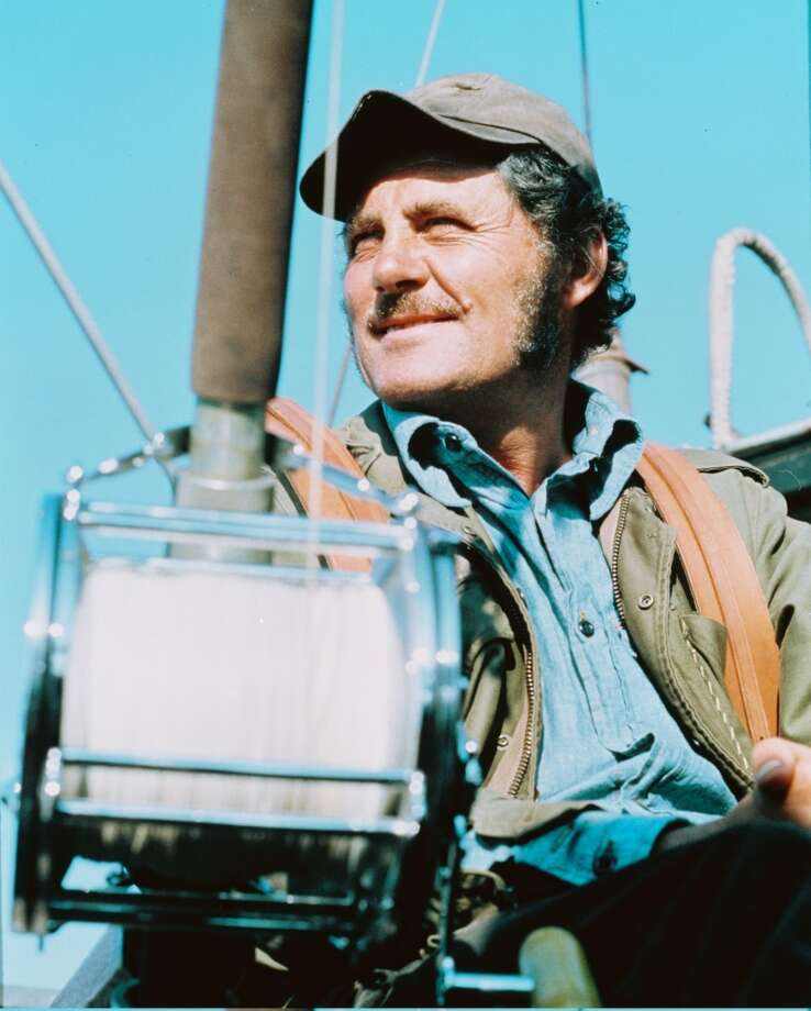 Robert Shaw (1927-1978), British actor, wearing a peaked cap, with the reel of a fishing rod in the foreground, in a publicity portrait issued for the film, 'Jaws', USA, 1975. The thriller, directed by Steven Spielberg, starred Shaw as 'Quint'. Photo: Getty Images