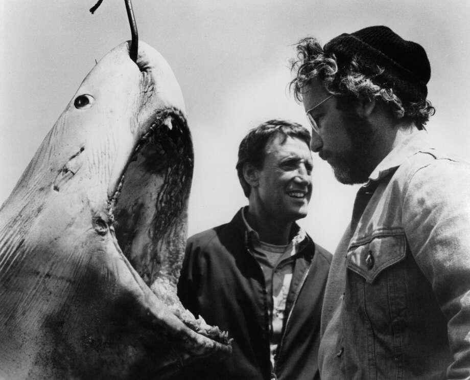 Roy Scheider and Richard Dreyfuss stand next to a giant man eating Great White Shark with a hook piercing through it in a scene from the film 'Jaws', 1975. Photo: Getty Images