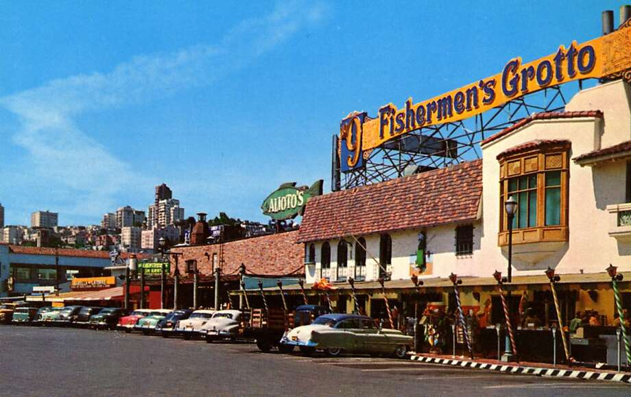 Vintage 1957 postcard showing the exterior of Fisherman's Grotto and the surrounding area and restaurants.  Vintage automobiles are parked in front of the building, the city is visible in the distance on the left. Photo: Curt Teich Postcard Archives