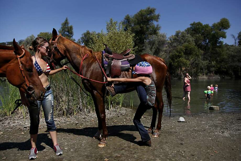 Tracey Sholtis helps Summer Green, 10, mount her horse at Del Valle Regional Park in Livermore, which includes a campground with horse stalls. Photo: Preston Gannaway, Special To The Chronicle