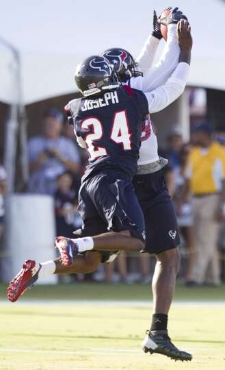 Wide receiver Andre Johnson (80) jumps in front of cornerback Johnathan Joseph (24) to catch a pass.