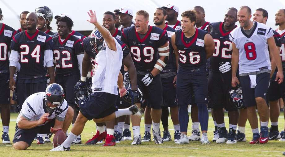 Players cheer on kicker Randy Bullock as he tries a long kick at the end of practice. Photo: Brett Coomer, Chronicle