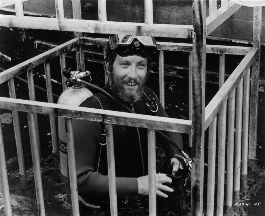 Richard Dreyfuss is lowered into the water in a diving cage in a scene from the film 'Jaws', 1975. Photo: Getty Images