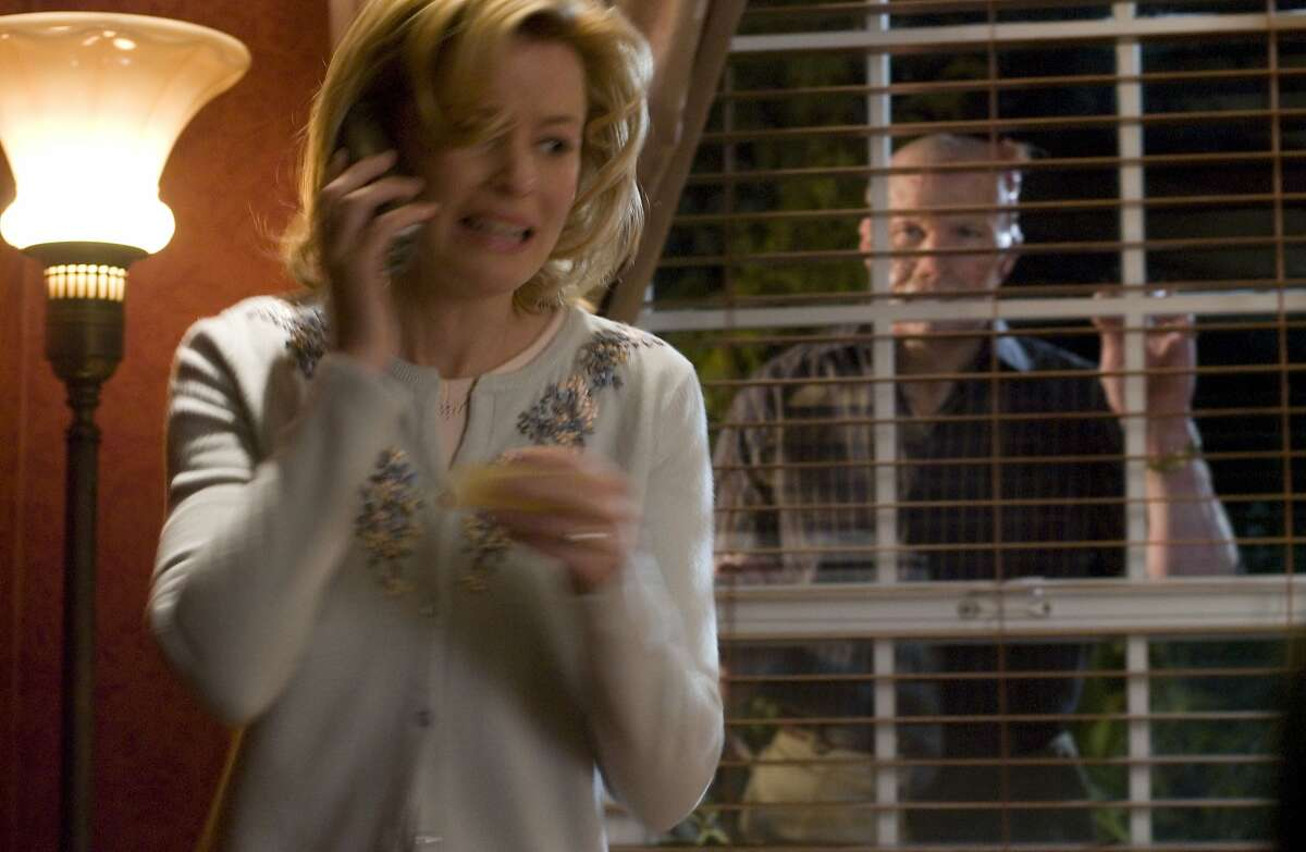 """Petrified Starla Grant (ELIZABETH BANKS) dials 911 while gruesome husband Grant Grant (MICHAEL ROOKER) looks on in """"Slither"""", a genre-bending horror film by Director James Gunn. """"Slither"""" will be released in theaters on March 31, 2006.Ran on: 03-31-2006"""
