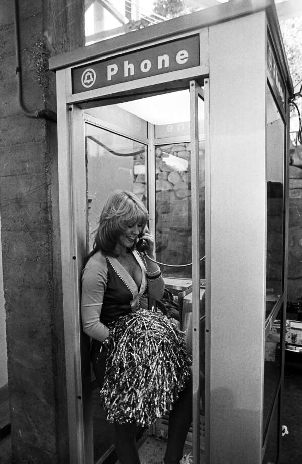 A Los Angeles Rams cheerleader makes a phone call at halftime during a 1987 Anaheim, California, football game. Photo: George Rose, Getty Images