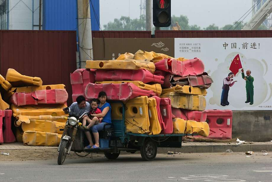Finders, keepers: A family salvages damaged road barriers in Beijing. Photo: Ng Han Guan, Associated Press
