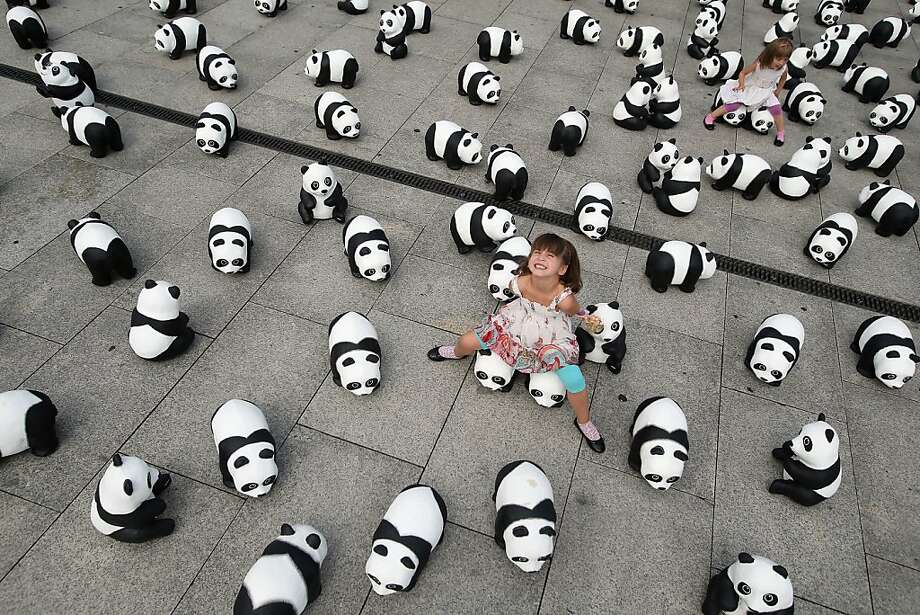 A somber message in black and white:Elaia and her sister, Lusitta (back), sit on some of the 1,600 Styrofoam pandas populating the front of Hauptbahnhof railroad station in Berlin. The World Wildlife Fund placed the bears in celebration of its 50th anniversary and to draw attention to the fact that only 1,600 pandas remain in the wild. Photo: Sean Gallup, Getty Images