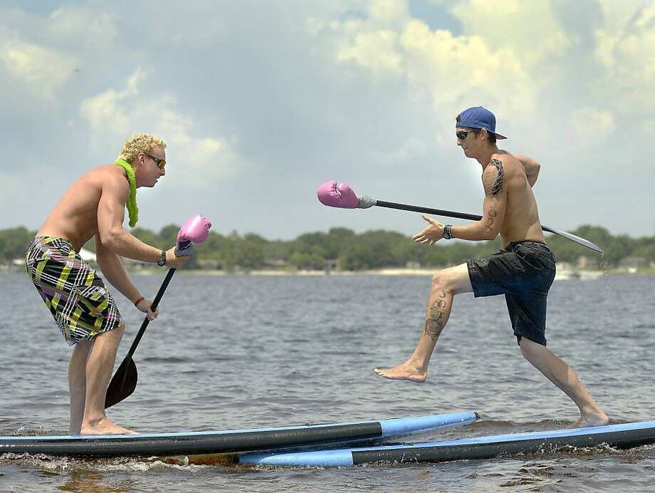 Avast, ye scalawag! Garrett Fletcher (left) and Blake Byerley attempt to knock each other off their paddleboards during an aquatic jousting match in Fort Walton 