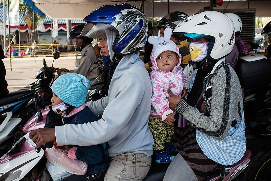 Sorry, kids, only grownups get to wear helmets: A scooter-riding family waits to board a 