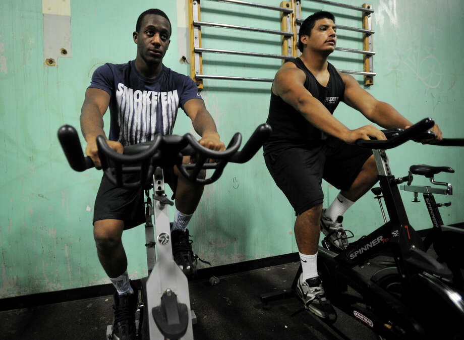 Football players Keyshawn Thomas, left, and Erick Cuatzo, try out exercise bikes, part of a large donation of exercise equipment to the Bridgeport high schools by the Jewish Community Center at Central High School in Bridgeport, Conn. on Tuesday, August 6, 2013. Photo: Brian A. Pounds / Connecticut Post
