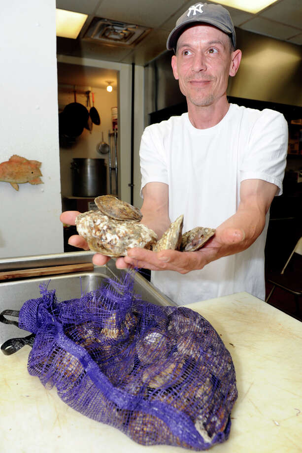 George Twigg, manager at Swanson's Fish Market in Fairfield, Conn., shows a quarantined bag of Blue Point Oysters, Aug. 6th, 2013. The oysters will not be sold, and will be returned to the store's supplier. Photo: Ned Gerard / Connecticut Post