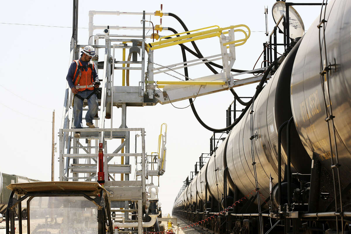 Workers unload crude oil from a tanker truck into railroad tankers at the Gardendale Railroad Inc. switching yard near Cotulla. Abandoned years ago, the yard has been transformed into a large rail interchange by Eagle Ford Shale activity.