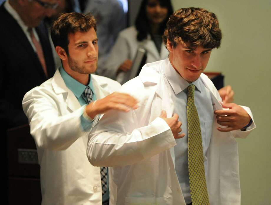 Second-year medical student Mark Chaskes of Buffalo helps incoming medical student Noah Joseph of Washington, D.C., put on his first white medical coat Tuesday, Aug. 6, 2013, during the White Coat Ceremony at Albany Medical College in Albany, N.Y. (Lori Van Buren / Times Union) Photo: Lori Van Buren / 00023415A