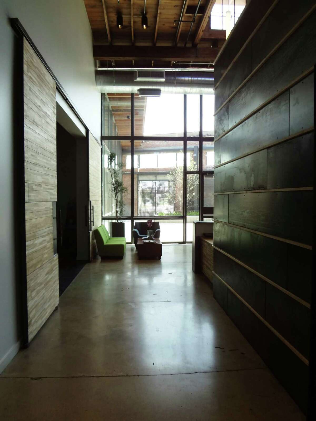 A hallway leads to the front reception area from the main offices of Overland Partners headquarters. The design of the adapted space called for wood, steel, glass and original concrete floors, washed and polished.
