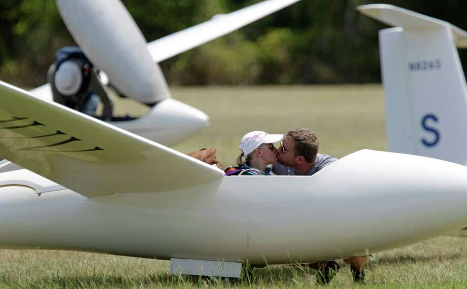 Sylvia Grandstaff  gets a kiss from her husband, Hugh Grandstaff, as she waits for her glider to be towed into the air during the Region 10 Championship at the Soaring Club of Houston Monday, Aug. 5, 2013, in Waller. Photo: Melissa Phillip, Houston Chronicle / © 2013  Houston Chronicle