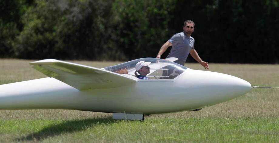 Hugh Grandstaff runs along holding up the wing of the gilder piloted by his wife, Sylvia Grandstaff, as she is towed into the air during the Region 10 Championship at the Soaring Club of Houston Monday, Aug. 5, 2013, in Waller. Photo: Melissa Phillip, Houston Chronicle / © 2013  Houston Chronicle
