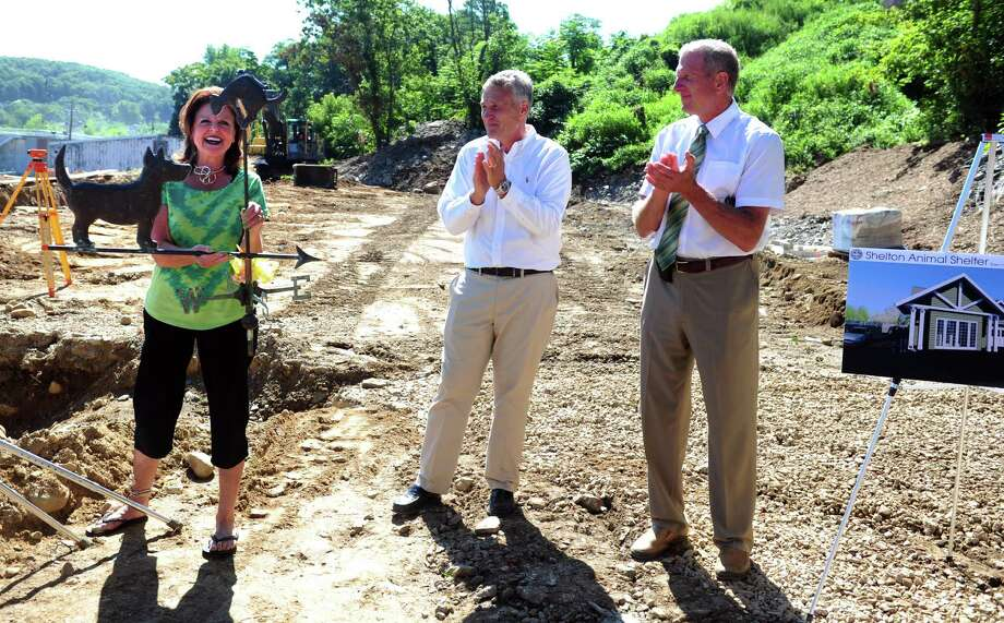 Animal Shelter Building Committee member Linda Hooper holds up a weathervane she found for the new shelter as Gregory Raucci, President Bismark Construction Co., and Shelton Mayor Mark Lauretti clap during a ground breaking ceremony Tuesday, Aug. 6, 2013 at the site on Brewster Lane in Shelton, Conn. Photo: Autumn Driscoll / Connecticut Post