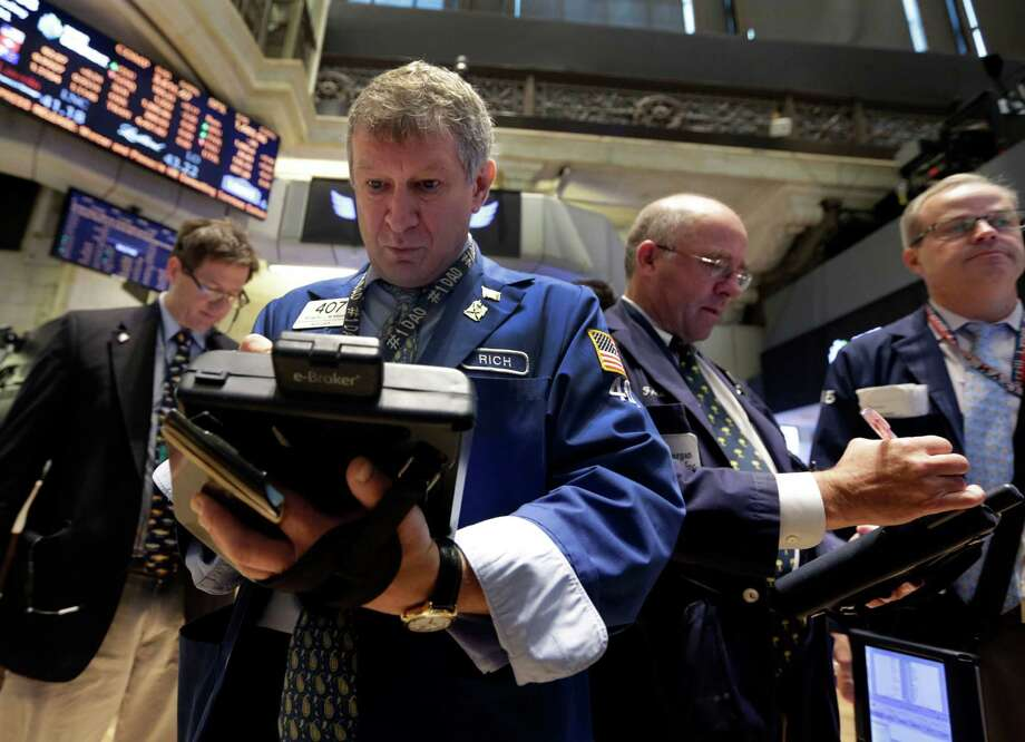 FILE - In this Wednesday, July 31, 2013, file photo, Richard Newman, second left, works with fellow traders on the floor of the New York Stock Exchange.  Stock futures bounced from earlier lows Tuesday, Aug. 6, 2013,  after the U.S. reported record exports in June and new data was released showing that home prices are rising sharply. (AP Photo/Richard Drew) ORG XMIT: NYBZ120 Photo: Richard Drew / AP