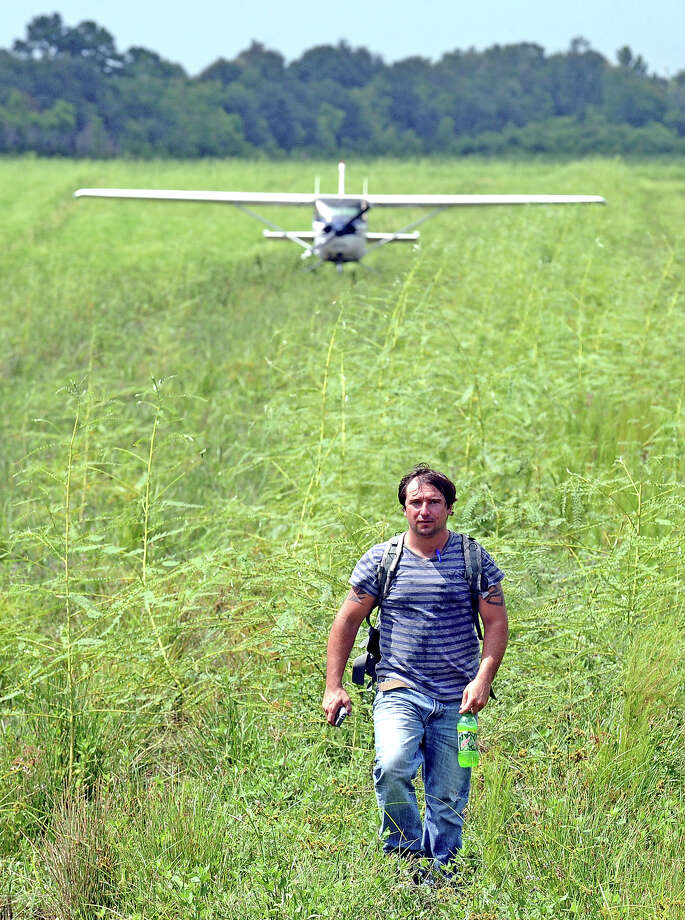 Chad Kennedy, 29, walks away the Cessna 152 that he landed 6 miles south of Interstate 10 off of Highway 365.  Kennedy was in route from Ellington Field in Houston to Lakefront Airport in New Orleans when he ran out of gas and brought the plane down in Fannett. Photo taken: Randy Edwards/The Enterprise Photo: Randy Edwards, Photojournalist / Enterprise