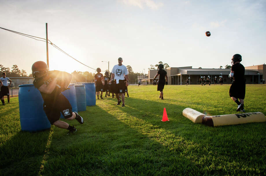 In the first day of fall practice, the pirates met on Vidor's field Monday. Head coach Jeff Mathews overlooks as Pirates practice footwork  by weaving through large barrels. Photo: Michael Reed / Michael Reed