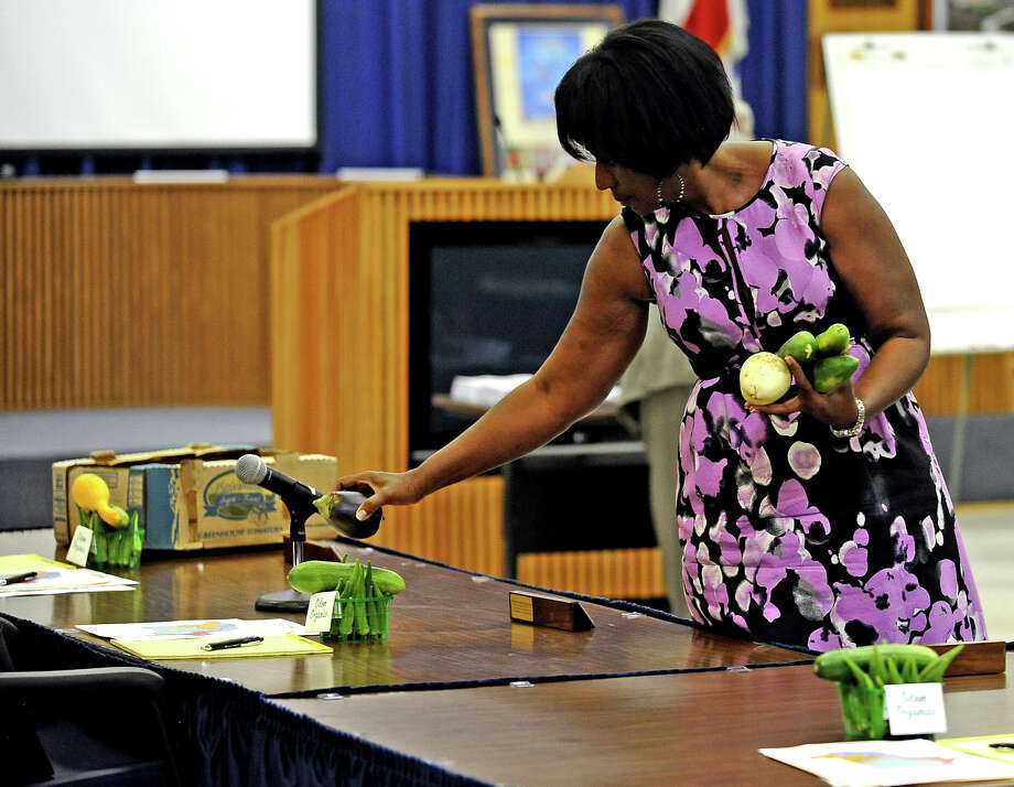 Special Assistant for Communications for BISD, Jessie Haynes, sets out produce from the Odom Organics garden before the meeting on Thursday, August 1, 2013. Photo taken: Randy Edwards/The Enterprise Photo: Randy Edwards