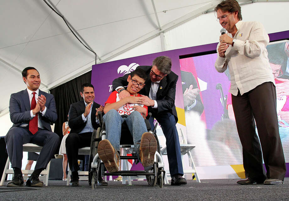 Governor Rick Perry awards the first patient badge to Denilson Alvarado as Teleton Foundation with Univision Communications holds a groundbreaking ceremonyy for a new child rehabilitation facility  in San Antonio on August 6, 2013.  Watching from left are Mayor Julian Castro, Univsion's Cesar Conde and Fernando Landeros from Teleton. Photo: TOM REEL