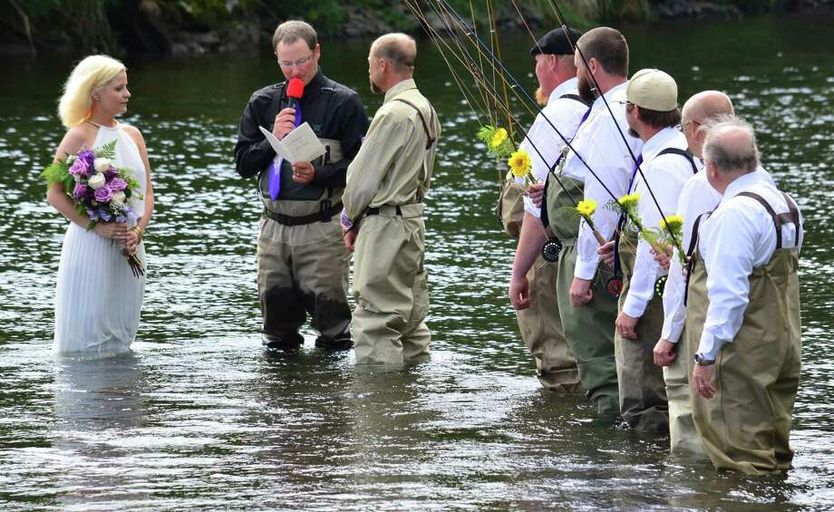 Groomsmen holding fly fishing rods watch as Kadie and Dake Schmidt exchange vows Saturday, Aug. 3, 2013 in Kodiak, Alaska's Buskin River. Photo: James Brooks, Associated Press / Kodiak Daily Mirror