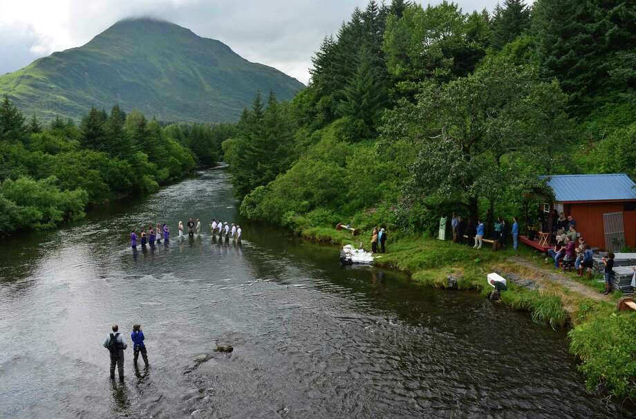 Accompanied by their wedding party, fishing guides Kadie Walsh and Dake Schmidt exchange vows in the middle of Kodiak, Alaska's Buskin River on Saturday, Aug. 3, 2013. In the background is Pillar Mountain. The fishing-themed ceremony included rings carried in the mouths of king salmon, a wedding party carrying fly fishing rods, and the married couple catching a pair of pink salmon together. Photo: James Brooks, Associated Press / Kodiak Daily Mirror