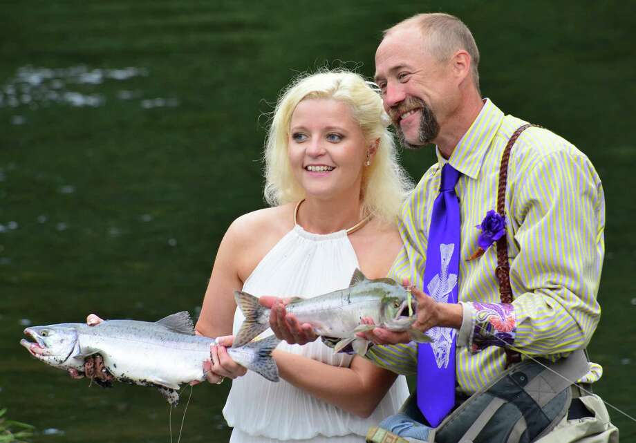 Kadie and Dake Schmidt hold a pair of pink salmon, their first fish caught together after their wedding Saturday, August 3, 2013, in Kodiak, Alaska's Buskin River. Photo: James Brooks, Associated Press / Kodiak Daily Mirror