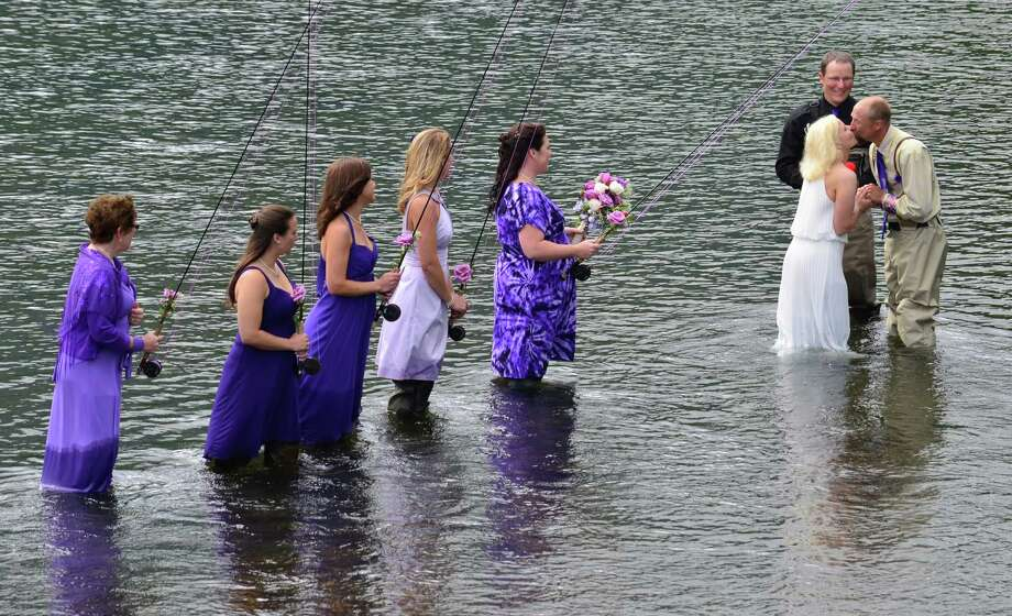 Bridesmaids look on as Kadie and Dake Schmidt, right, exchange a kiss at the end of their wedding ceremony Saturday, Aug. 3, 2013, in Kodiak, Alaska's Buskin River. The wedding was officiated by Jason Fox, a fisherman who obtained a special certificate allowing him to legally conduct the ceremony. Photo: James Brooks, Associated Press / Kodiak Daily Mirror