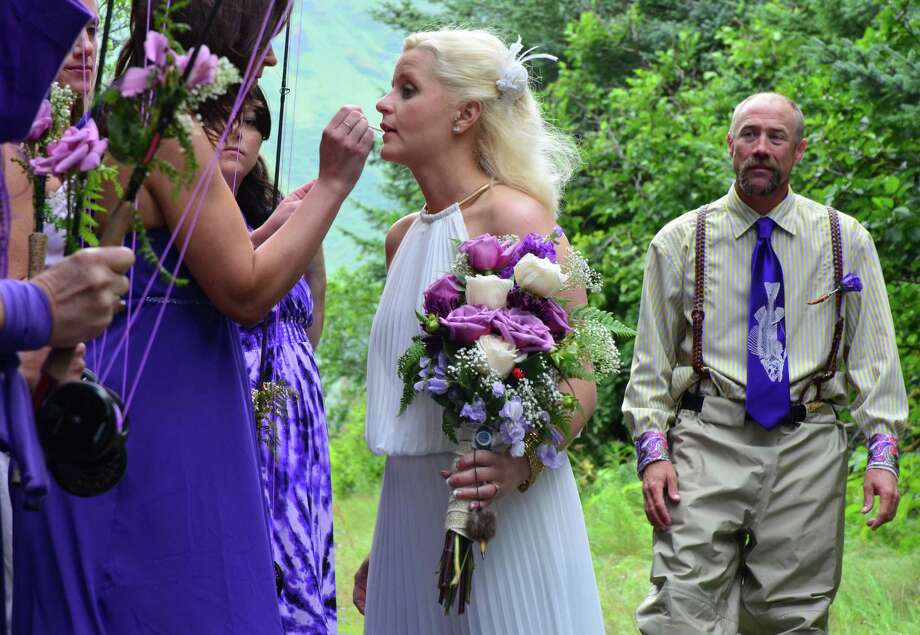 A bridesmaid helps Kadie Walsh with another layer of lip gloss as Dake Schmidt watches before their wedding ceremony Saturday, August 3, 2013 at Kodiak, Alaska's Buskin River. Photo: James Brooks, Associated Press / Kodiak Daily Mirror
