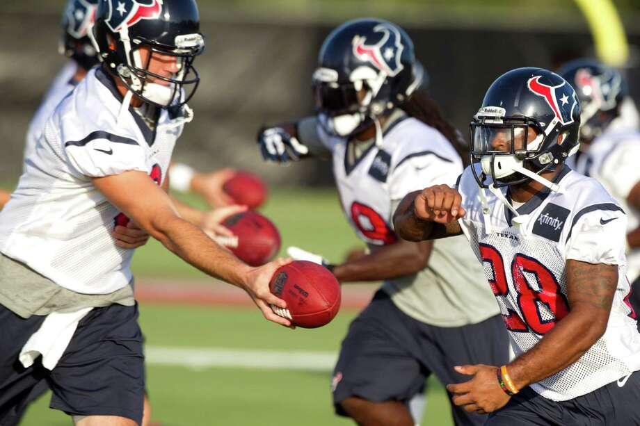 Dennis Johnson, right, is trying to impress the Texans enough that they will trust him to take handoffs from Matt Schaub in live action despite being a rookie. He also could be a factor on kick returns. Photo: Brett Coomer, Staff / © 2013 Houston Chronicle