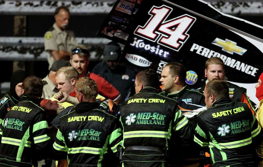 In this Aug. 5, 2013 photo, three-time NASCAR champion Tony Stewart, third from left, is loaded into an ambulance after being involved in a four-car wreck at Southern Iowa Speedway in Oskaloosa, Iowa. A spokesman for Stewart said the 42-year-old driver broke his right tibia and fibula and had surgery after he was transported to a local hospital.  (AP Photo/The Des Moines Register, Mary Willie) ORG XMIT: IADES101 Photo: Mary Willie / The Des Moines Register