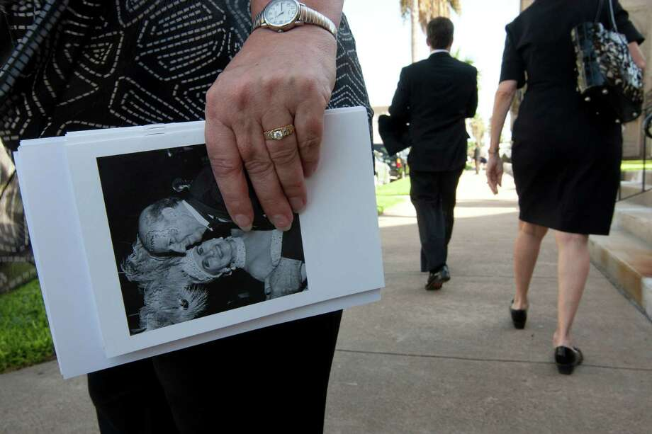 A woman holds a funeral program as mourners file into Trinity Episcopal Church to attend a private memorial service for George Mitchell Tuesday, Aug. 6, 2013, in Galveston. Photo: Johnny Hanson, Houston Chronicle / © 2013  Houston Chronicle