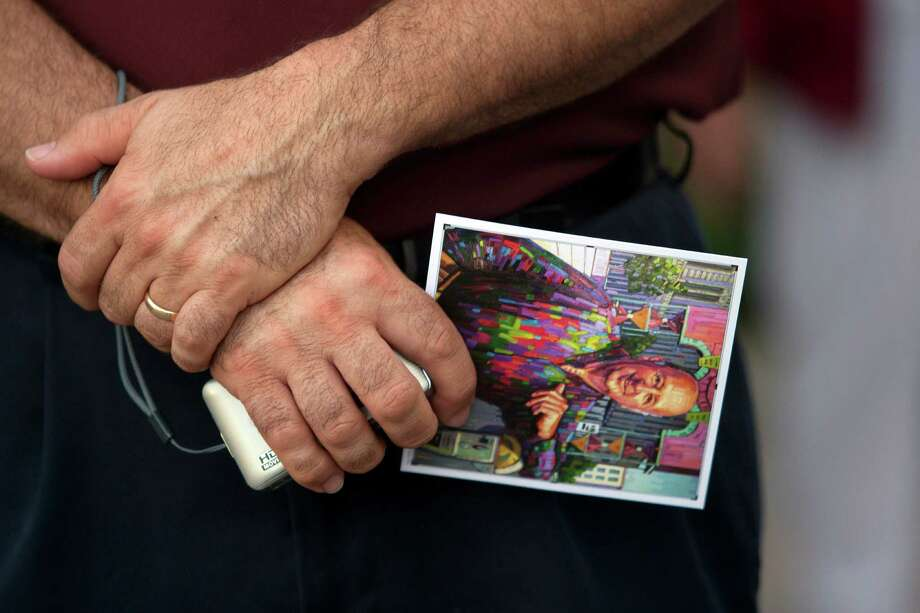 A mourner holds an image of George Mitchell as hundreds gather at Saengerfest Park during a public memorial service for George Mitchell Tuesday, Aug. 6, 2013, in Galveston. Photo: Johnny Hanson, Houston Chronicle / © 2013  Houston Chronicle