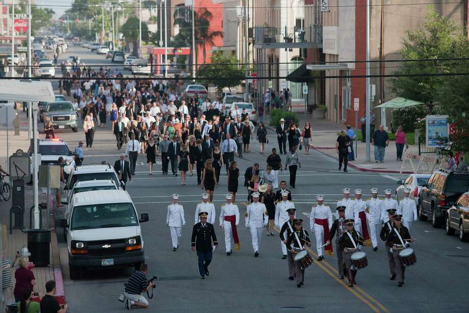 Led by the Texas A&M Ross Volunteer Company and drum line, hundreds of mourners walk down Tremont Street to attend a public memorial service for George Mitchell at Saengerfest Park at Tuesday, Aug. 6, 2013, in Galveston. Photo: Johnny Hanson, Houston Chronicle / © 2013  Houston Chronicle