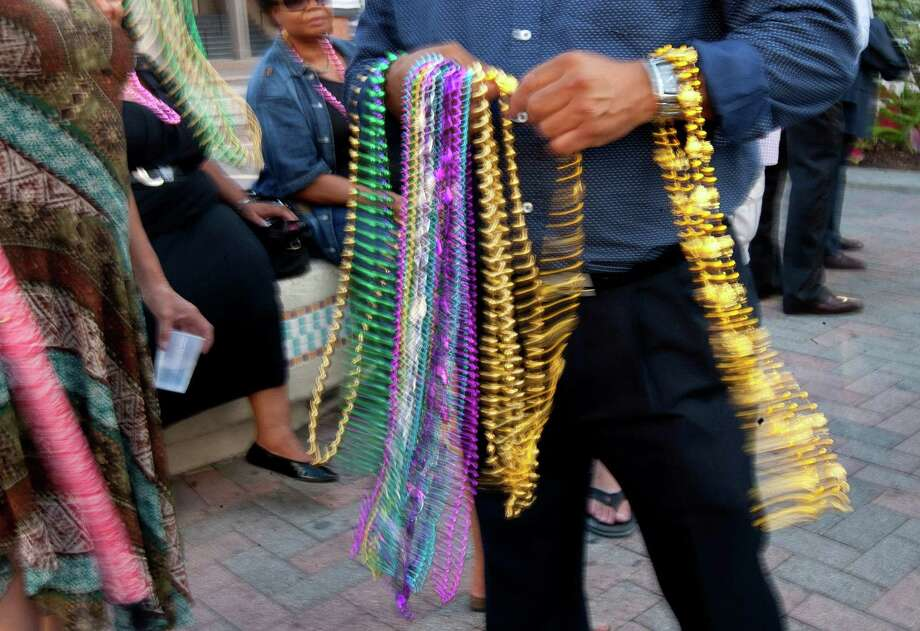 Known for making Galveston's Mardi Gras celebration what it is today, mourners were given beads during a public memorial service for George Mitchell at Saengerfest Park Tuesday, Aug. 6, 2013, in Galveston. Photo: Johnny Hanson, Houston Chronicle / © 2013  Houston Chronicle