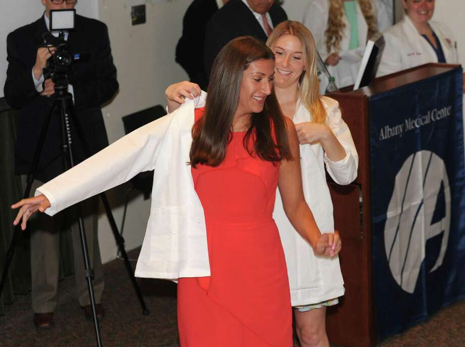 Second year medical student Nicole Umanoff of Long Island helps incoming medical student Krista Morales of Clifton Park put on her first white medical coat during the OWhite Coat CeremonyO at Albany Medical College on Tuesday, Aug. 6, 2013 in Albany, N.Y. (Lori Van Buren / Times Union) Photo: Lori Van Buren / 00023415A